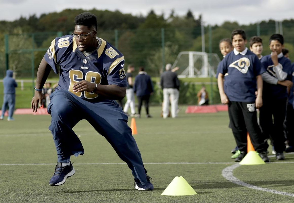 Los Angeles Rams guard Jamon Brown takes part in a drill during an NFL community event for schoolchildren at Surrey Sports Park in Guildford, England, Tuesday, Oct. 18, 2016. The Los Angeles Rams are due to play the New York Jets at Twickenham stadium in London on Sunday in a regular season NFL game. (AP Photo/Matt Dunham)